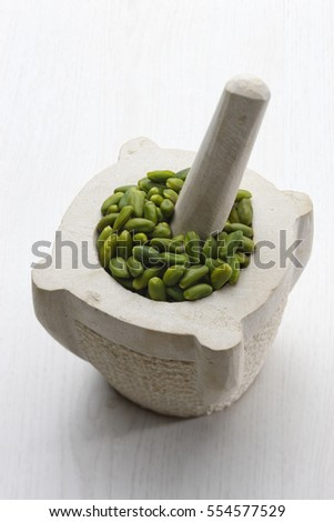 Skinned pistachio in a stone pestle on a white wooden table