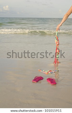 Skinny dipping concept shot showing a woman's arm dropping her top on the beach - stock photo
