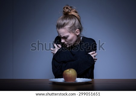 Skinny girl afraid of eating and obsessed with weight - stock photo