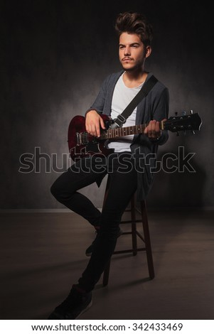 skinny rocker playing guitar while sitting in studio background and looking away