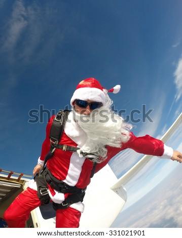 Skinny Santa jumping from the plane - stock photo
