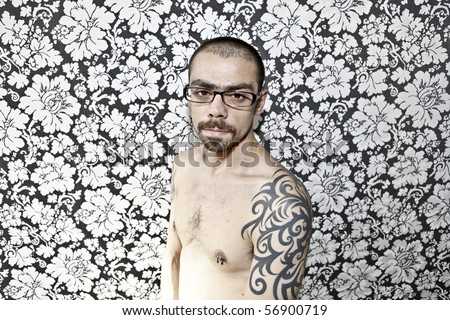 skinny tattoo guy on floral background - stock photo