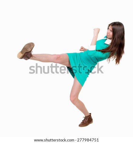skinny woman funny fights waving his arms and legs. Isolated over white background.  Girl in leather boots strikes. - stock photo