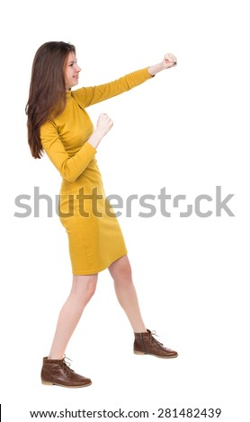 skinny woman funny fights waving his arms and legs. Rear view people collection.  backside view of person.  Girl engineer in the yellow dress standing right side and hit his left hand. - stock photo
