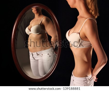 Skinny woman seeing herself fat in a mirror - stock photo
