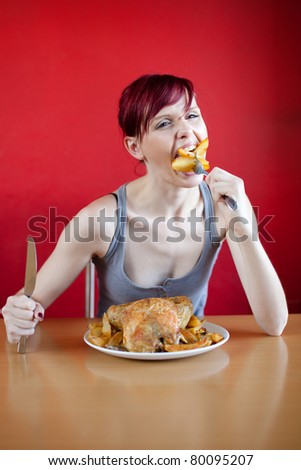 Skinny woman with a whole chicken on her plate stuffing herself with baked potatoes - stock photo