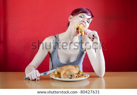 Skinny woman with a whole chicken on her plate stuffing herself with baked potatoes. Diet series. - stock photo
