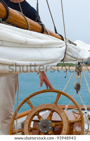 Skipper at the wheel of a classic wooden schooner, leaving for a sail - - stock photo
