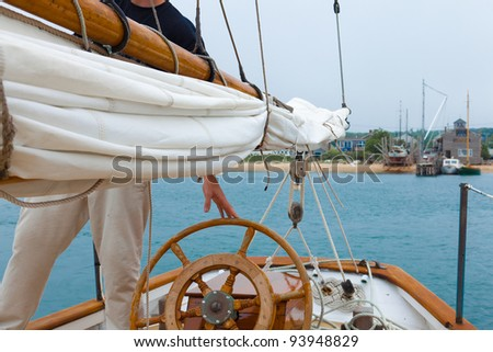 Skipper at the wheel of a vintage wooden sailboat - stock photo