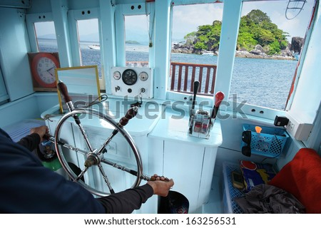 Skipper hands on a steering wheel of a boat motoring in tropical sea - stock photo