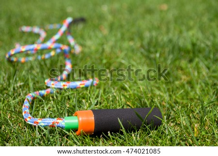 Skipping rope on green grass background. Fitness training in the open air with jumping rope