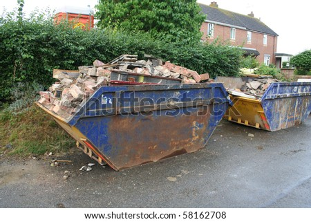 Skips filled with rubble outside a demolished building. - stock photo