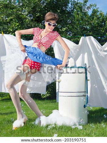 Skirt caught by wringer, pin up style photo of woman with vintage washing machine doing laundry outdoor - stock photo