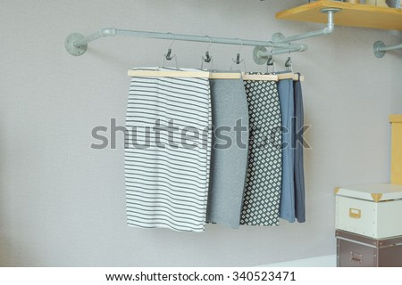 skirts hanging on industrial style clothes rail in walk in closet - stock photo