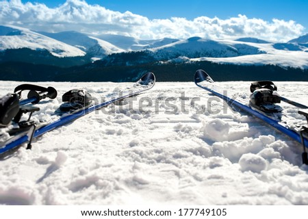 Skis and equipment on mountain slope in winter season. Winter landscape with snow and mountains - stock photo