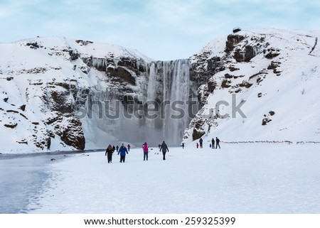 Skogafoss Waterfall Attracts Visitors during Winter in Iceland - stock photo