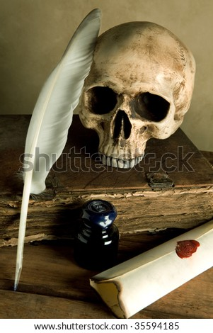 Skull and antique book on a table with old parchment and quill