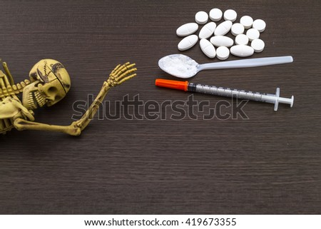Skull and drugs with insulin syringe. Next to them are a spoon with white powder, which is similar to heroin on wooden  background,touch - up in still life concept. - stock photo