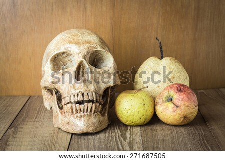 skull and sear fruit still life on wood background - stock photo