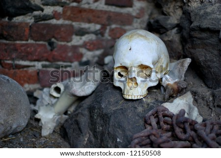 Skull, Bones and Handcuffs in Castle Dungeon. - stock photo