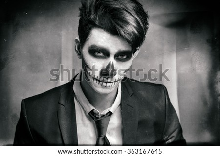 Skull make up portrait of young man in studio. Digital manipulation to simulate analogic film effect. - stock photo