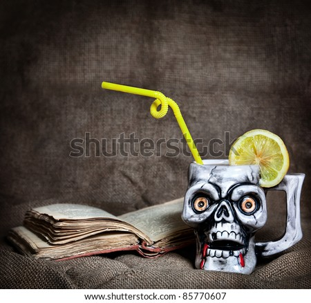 Skull mug with lemon and yellow stick near old book at textured background on Halloween party - stock photo