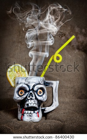 Skull mug with lemon and yellow stick with steam from inside at textured background on Halloween party