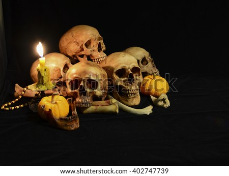 Skull on pile of dry pumpkin and bone pile with candle light , on black background/ Still life style