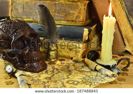 Skull with burning candle, pirate map and old books - stock photo