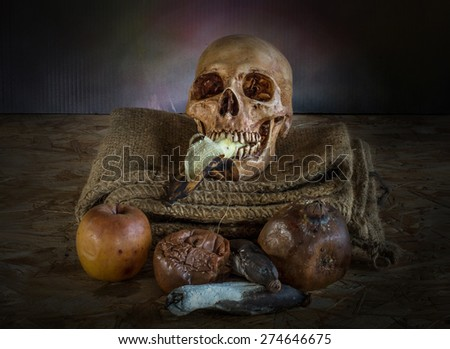 Skull with dried and rot fruit, on wood plate, Still Life - stock photo
