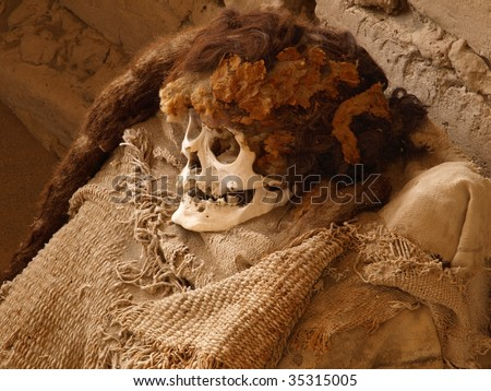Skull with hair and textiles of an ancient Nazca human in tomb at the Cemetery de Chauchilla in Nazca, Peru, South America. - stock photo