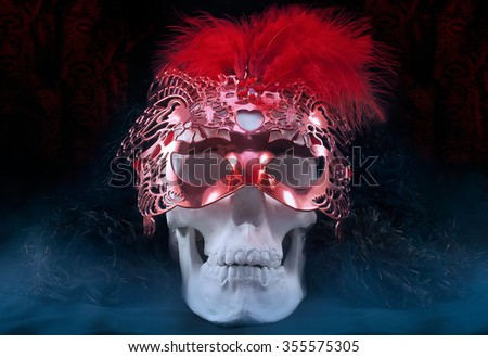 Skull with venetian carnival mask.Mystical white skull with fur collar and mysterious carnival venetian red mask with feathers.