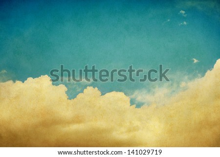 Sky and billowing clouds on a textured background with vintage colors.  Image displays a pleasing paper grain and texture when viewed at 100 percent. - stock photo