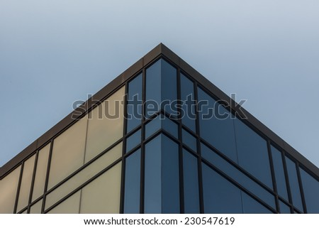 Sky and clouds reflect in the windws of a futuristic office building - stock photo