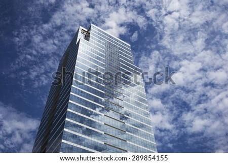 Sky and clouds reflecting in skyscraper windows - stock photo