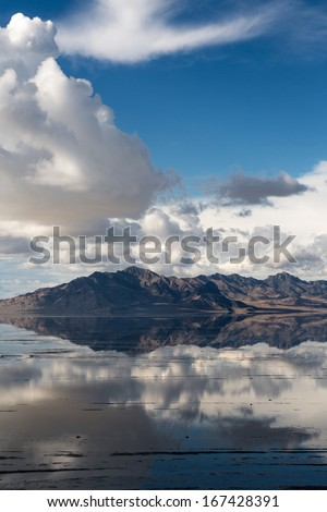 Sky and mountains creating a mirror image in the rain soaked Bonneville Salt Flats in Utah, USA - stock photo