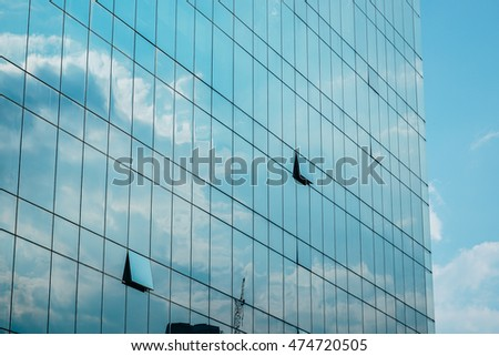sky, clouds and building reflecting on a building with mirrored glass