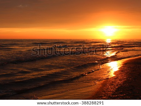 Sky of sea sunset. Beautiful summer golden sunset above the black sea.with calm waves and reflection of sun on the beach. Sochi, Russia - stock photo