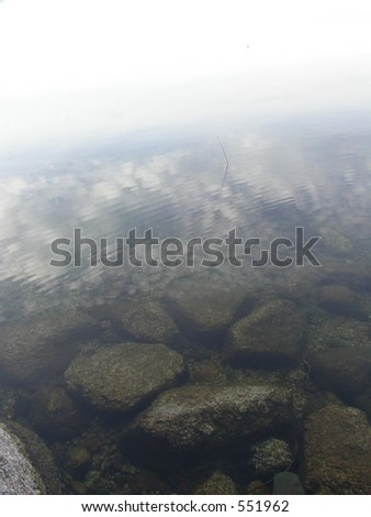 Sky reflected on pond with rocks visible beneath the water