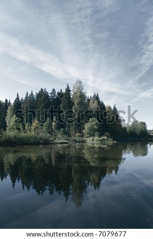sky reflecting in a calm northern lake - stock photo