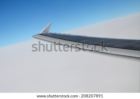 Sky scenery: wing of a passenger jet in front of white clouds and blue sky - stock photo