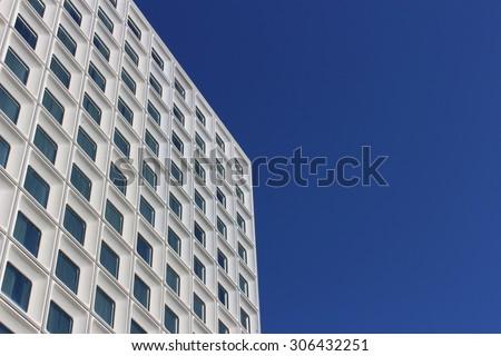 Sky scraper tower block, white against deep blue sky. Repetitive pattern of square windows. Perth, Australia. - stock photo