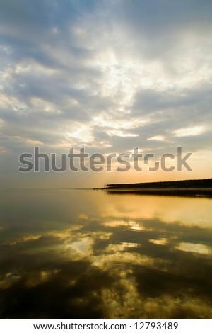 sky, sea and forest coast on horizon - stock photo