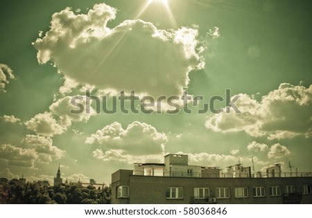 Sky with clouds and sun over the Warsaw. View from The University of Warsaw Library's roof. Retro style. - stock photo