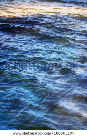 sky with clouds reflected on the water surface with waves