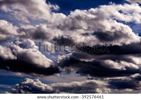 Sky with grey and black clouds before storm with blue sky in background - stock photo