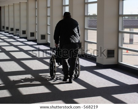 Skycap brings a wheelchair to a traveler needing assistance - stock photo