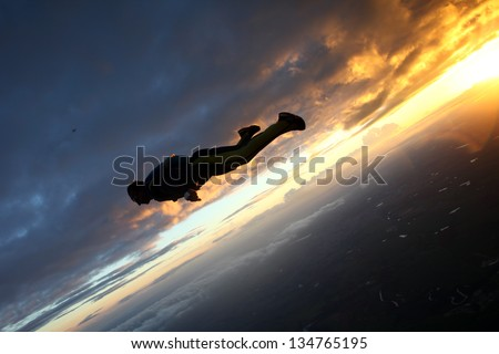 Skydive wing suit sunset - stock photo