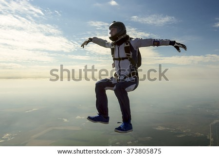 Skydiver athlete performs figures in freefall. - stock photo