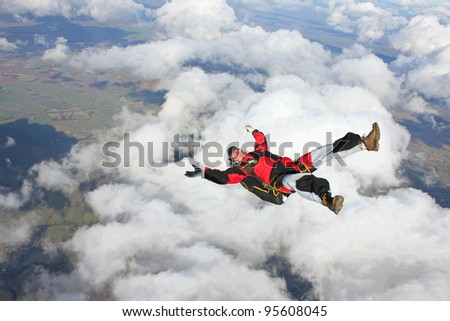 Skydiver falling on his back through the air - stock photo
